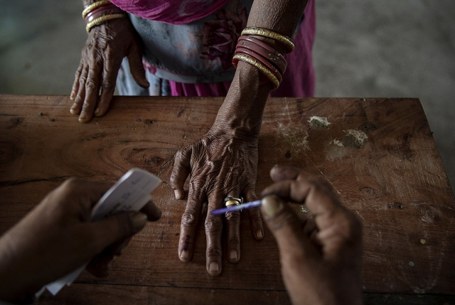 An Indian woman has her finger inked by an elections worker before voting at a polling station on April 17, 2014. (Kevin Frayer/Getty Images)
