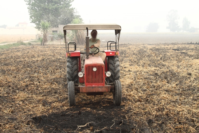 A farmer ploughing in evidence of paddy straw burnt in fields at Noorpur Bet village in Ludhiana. Photo by Vivian Fernandes on 1 November, 2016.