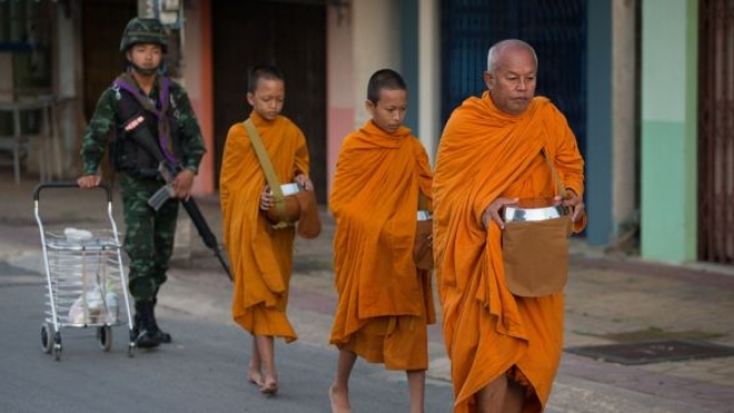 Buddhist monk seeks alms in southern Thailand.