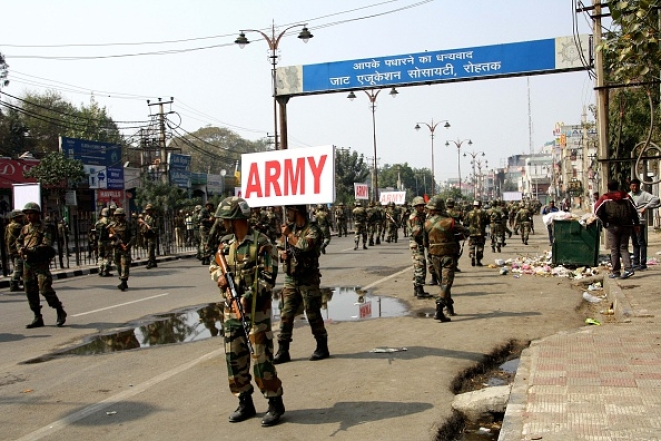 Army personnel take out a flag march to handle the situation as Jat community protests on the roads demanding reservations in government services on 20 February 2016 in Rohtak, India. (Manoj Dhaka/Hindustan Times via GettyImages)