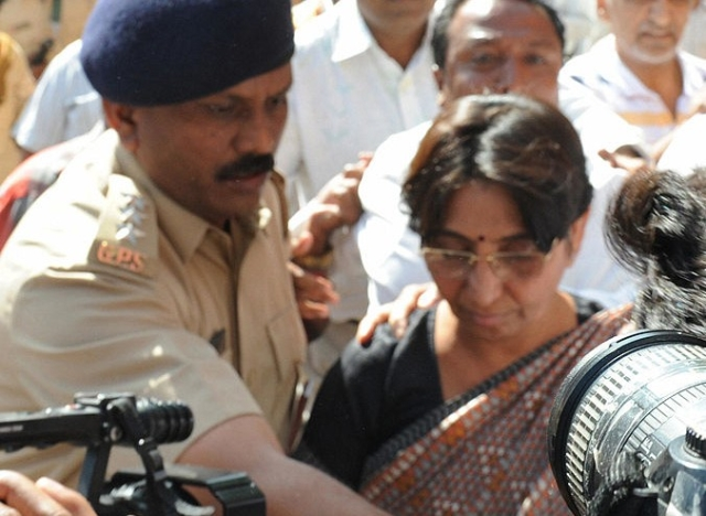 An Indian police officer escorts Kodnani after she surrendered to a special investigation team in Gandhinagar on 27 March 2009. (SAM PANTHAKY/AFP/Getty Images)
