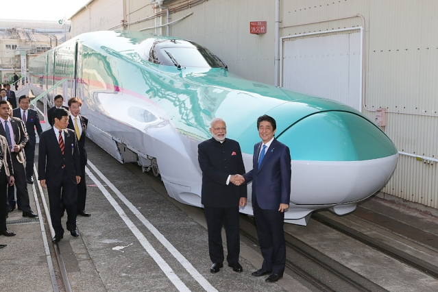 Prime Minister Narendra Modi  and his Japanese counterpart Shinzo Abe  shake hands in front of a shinkansen train during their inspection at a bullet train manufacturing plant in Kobe, Hyogo prefecture on 12 November 2016. (JIJI PRESS/AFP/Getty Images)