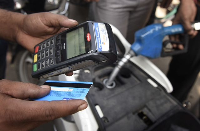 The people using debit card to pay for the petrol at Petrol Pump in Mayur Vihar on November 9, 2016 in New Delhi, India. In a surprise announcement late Tuesday, Prime Minister Narendra Modi banned 500 rupee ($7.50) and 1,000 rupee notes effective midnight, sweeping away 86 percent of total currency in circulation. In panic people flocked to their nearest ATMs, Petrol Pumps and Railway Stations to get change cash. (Sushil Kumar/Hindustan Times via Getty Images)