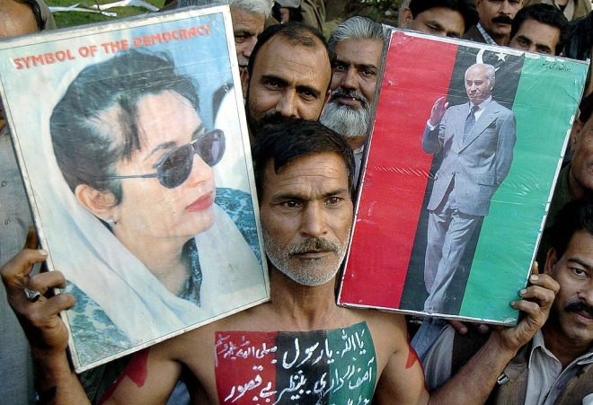 An activist of the Pakistan Peoples Party holds pictures of former prime minister Benazir Bhutto and his father former prime minister Zulfiqar Ali Bhutto in Lahore during a rally. (ARIF ALI/AFP/GettyImages)