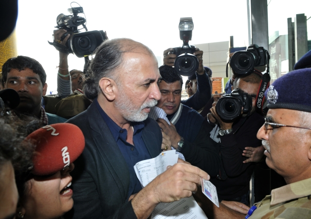Tarun Tejpal shows his identity card to an official as he enters the airport in New  Delhi. (STRDEL/AFP/Getty Images)