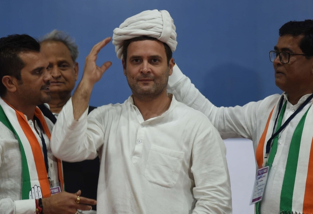 Congress workers present a turban to Rahul Gandhi during a public meeting at Varachha Surat, on 3 November in Gujarat, India. (Vijayanand Gupta/Hindustan Times via GettyImages)