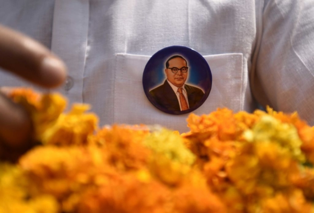People buy posters and souvenirs to pay tribute to Dr Bhim Rao Ambedkar on his 126 birth anniversary at Parliament Street in New Delhi. (Sushil Kumar/Hindustan Times via Getty Images)