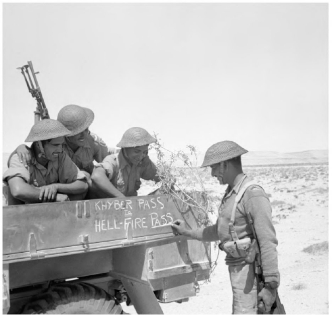"""Soldiers of the Fourth Indian Division decorate the side of their lorry with the words: """"From Khyber Pass to Hellfire Pass"""". Hellfire Pass was the nickname for the strategic Al-Halfaaya Pass in Egypt which the Indians tried to wrest from the Germans."""